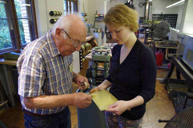 Alter Meister und junge Meisterin beim Betrachten einer guillochierten Platte...